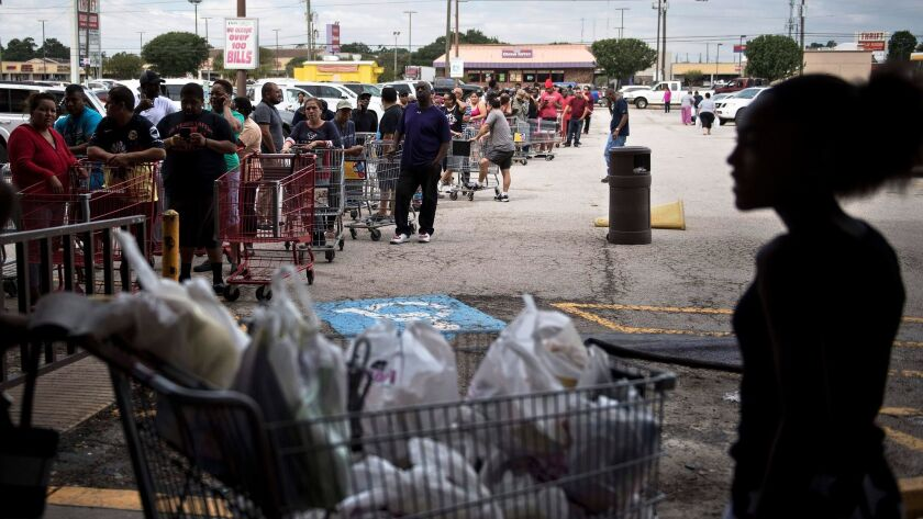 People wait in line to buy groceries at a Food Town during the aftermath of Hurricane Harvey in Houston, Texas.