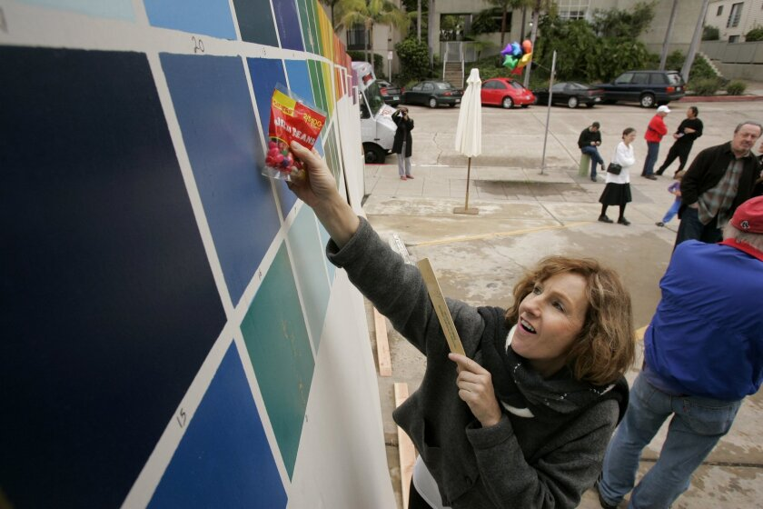 Elaine Wilder of Tucson, Ariz., picks her favorite color from samples posted near the wall in La Jolla displaying Roy McMakin's mural.  CHARLIE NEUMAN • UT