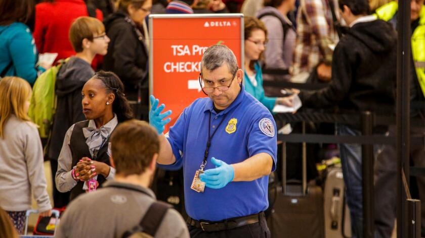 Un agente de TSA vigila a los viajeros a través de los controles de seguridad de LAX_ (Irfan Khan / Los Angeles Times).