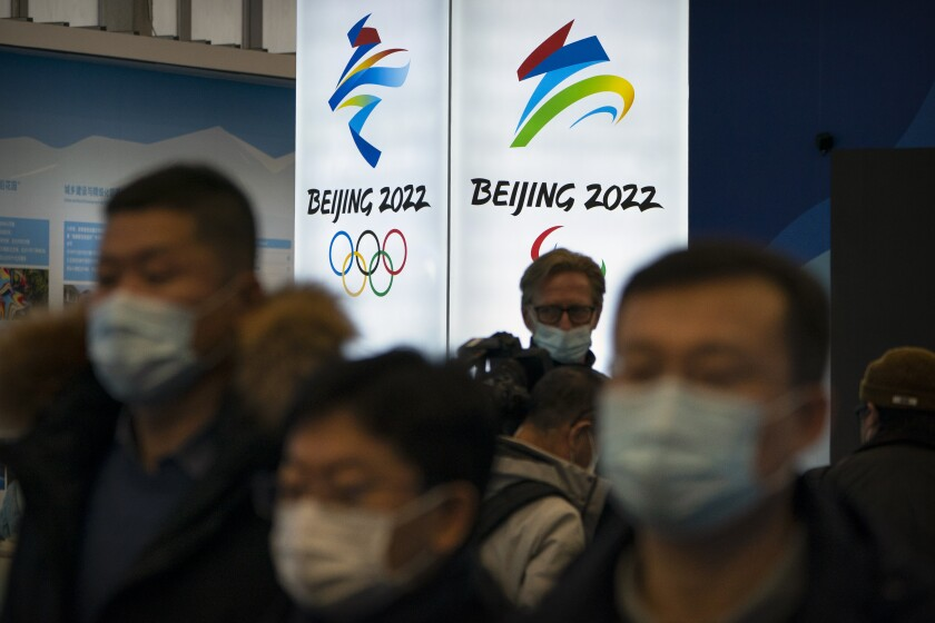 People wearing face masks look at an exhibit with their backs toward a Beijing 2022 sign.