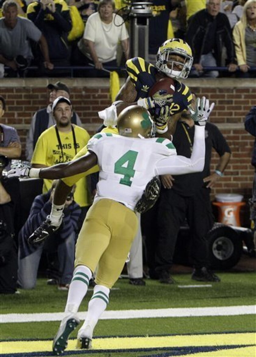 Michigan wide receiver Roy Roundtree catches the game-winning touchdown pass over Notre Dame cornerback Gary Gray (4) during the closing seconds of the fourth quarter of an NCAA college football game in Ann Arbor, Mich., Saturday, Sept. 10, 2011. Michigan won 35-31.(AP Photo/Carlos Osorio)