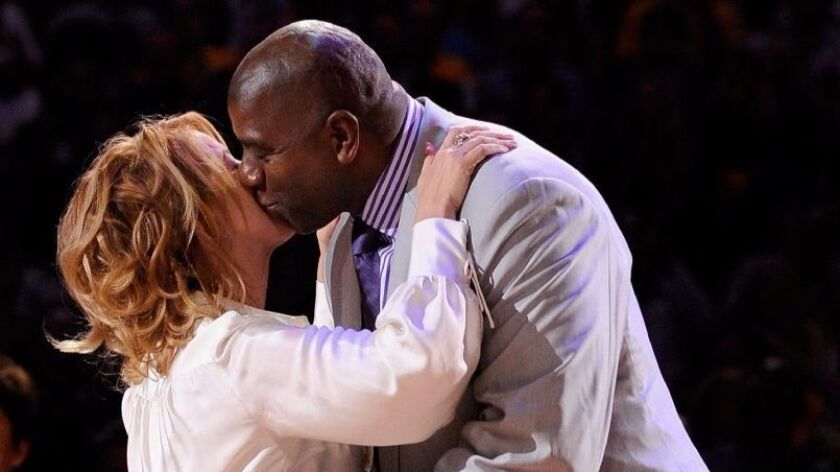 Jeanie Buss and Magic Johnson embrace each other during the Lakers' 2009 NBA championship ring prese