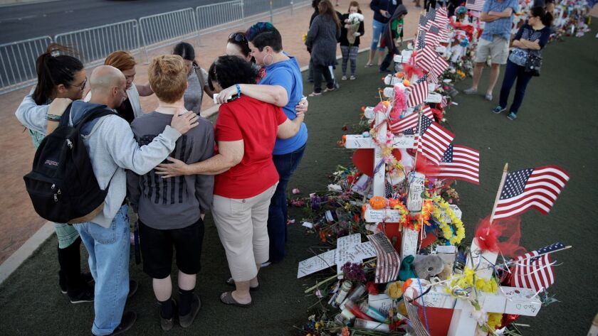 People pray at a makeshift memorial for victims of the mass shooting in Las Vegas. With no clear explanation for what prompted gunman Stephen Paddock to kill 58 concert-goers, it's difficult for the nation to move on, experts say.