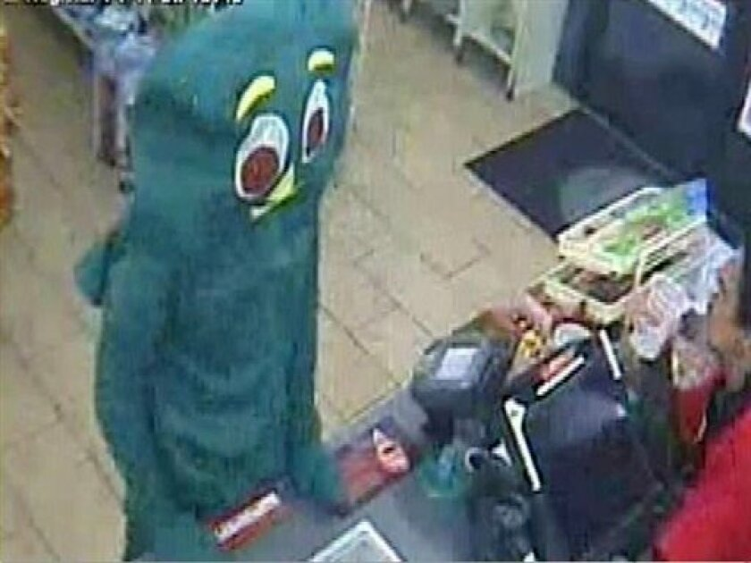 In this surveillance video taken Sept. 5, 2011, and released by  San Diego police, a suspect dressed like Gumby tells a convenience store clerk he is being robbed. (AP Photo/San Diego Police Department)