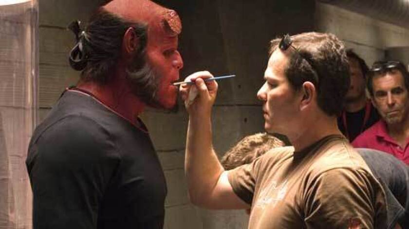 "PAINT JOB: Makeup effects designer Mike Elizalde touches up Ron Perlman, who portrays the ""Hellboy II"" title character."