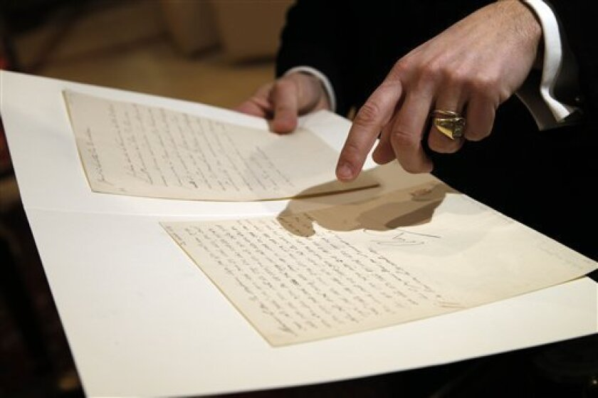 """In this photo taken Wednesday, Nov. 28, 2012, auction house associate Jean-Christophe Chataigniera holds up a letter dictated and signed by Napoleon in secret code that declares his intentions """"to blow up the Kremlin"""" during his ill-fated Russian campaign is displayed in Fontainebleau, outside Paris. The rare letter, written in unusually emotive language, sees Napoleon complain of harsh conditions and the shortcomings of his grand army. The letter goes on auction Sunday, Dec. 2, 2012. (AP Photo/Christophe Ena)"""