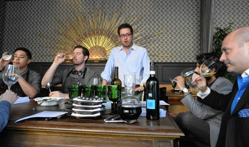 Jared Hooper, center, the sommelier and wine director at Faith & Flower, briefs his his staff about wines being added to the wine list.