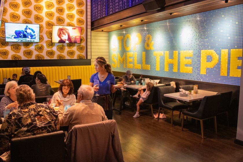 Diners try out the new menu Nov. 7 at Cohn Restaurant Group's just-unveiled Pacific Social in Carmel Valley. The Italian-made tile wall mural highlights the new American restaurant's cream and baked fruit pies, which are made in-house daily.