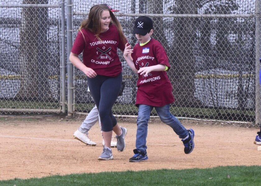 Lily Stratton runs the bases with a 'Tournament of Champions' participant. Her Girl Scout Gold Award was the creation of a baseball event for kids with special needs.