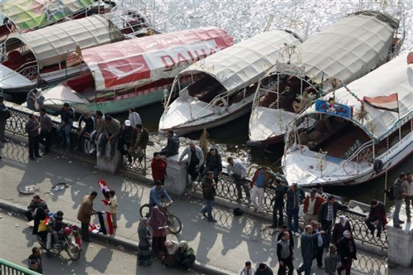 Egyptian anti-government protesters gather in front of Nile boats near the Egyptian television headquarters in Cairo, Egypt, Friday, Feb. 11, 2011. Egypt's military seemed to throw its weight Friday behind President Hosni Mubarak's plan to stay in office until September elections while protesters m