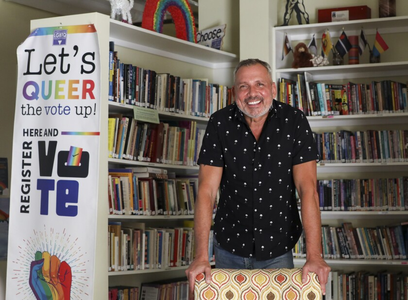 Max Disposti, founder and executive director of the North County LGBTQ Resource Center, leans against the back of a chair