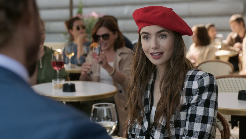 """Lily Collins, in beret, sits at a cafe table with a glass of white wine in """"Emily in Paris"""""""
