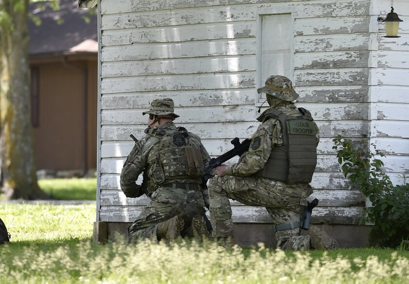 A tactical team from the Missouri Highway Patrol monitor a house in Sedalia, Mo. Thursday, May 21, 2015 where police thought a suspect in the slayings of Sandra Sutton and Zachary Wade Sutton had taken shelter. The Suttons were found dead earlier Thursday in Clinton, Mo. The police raided but failed to find anyone inside the home. (Jill Toyoshiba/The Kansas City Star via AP)