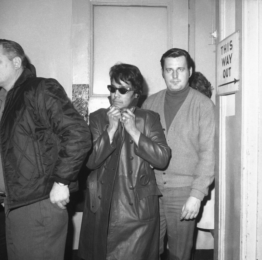 Dollree Mapp is escorted into the New York Police Department's 105th Precinct in this undated photo.
