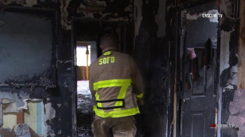 Firefighters work inside a home gutted by flames where a man was injured Thursday evening in Imperial Beach.