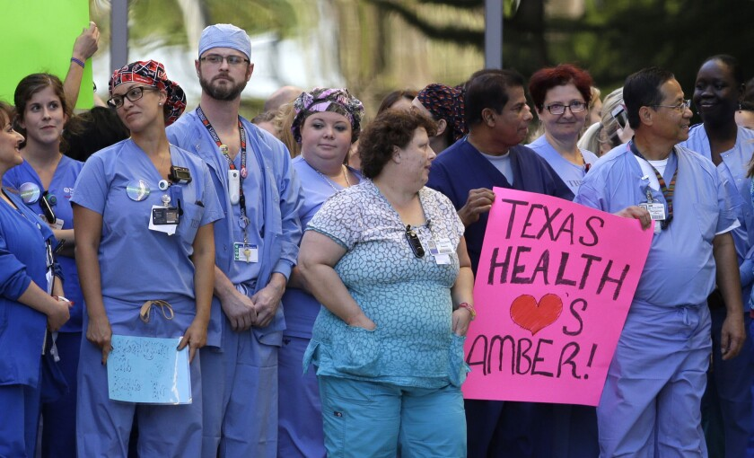 Workers at Texas Health Presbyterian Hospital in Dallas assemble Thursday. One holds a sign supporting nurse Amber Vinson, who contracted Ebola after treating a patient there.