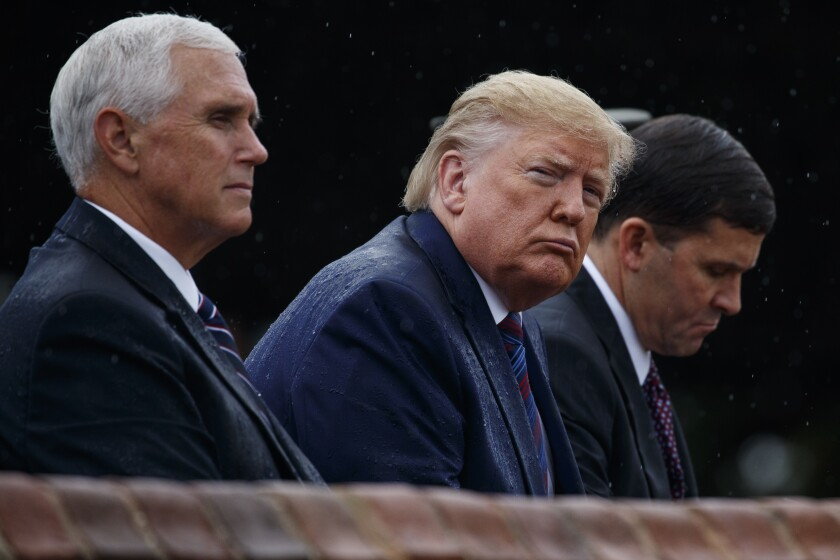 From left, Vice President Mike Pence, President Donald Trump, and Defense Secretary Mark Esper, participate in an Armed Forces welcome ceremony for the new chairman of the Joint Chiefs of Staff, Gen. Mark Milley, Monday, Sept. 30, 2019, at Joint Base Myer-Henderson Hall, Va. (AP Photo/Evan Vucci)