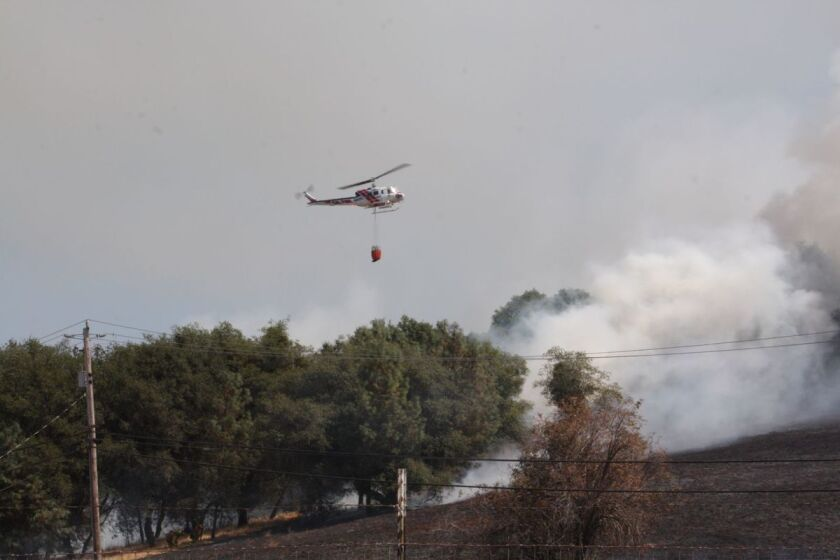 A helicopter prepares to make a water drop on the Willow Fire in Calveras County.