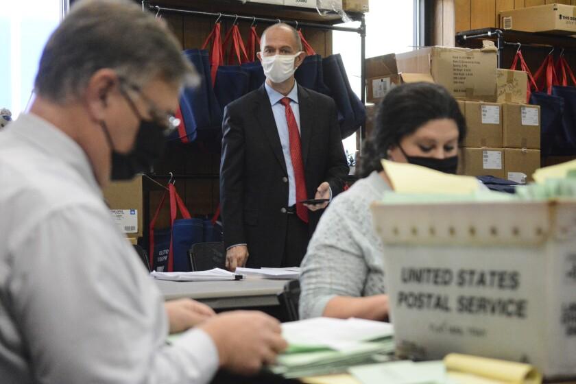 A Republican poll watcher observes an election bureau director and staffer open provisional ballots.