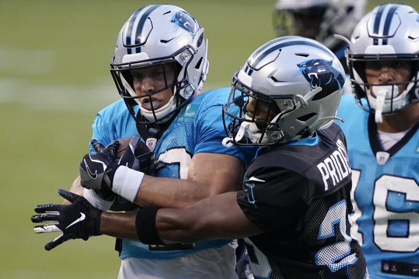 Carolina Panthers running back Christian McCaffrey, left, is hit by cornerback Troy Pride Jr.