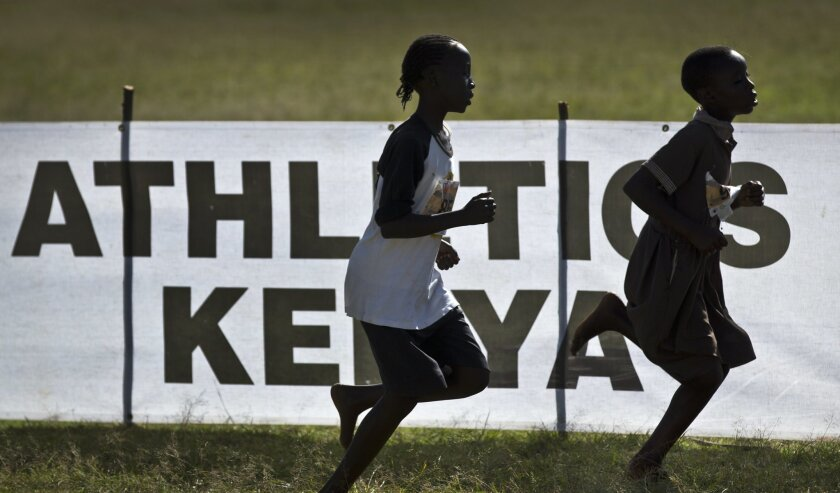 In this photo taken Sunday, Jan. 31, 2016, junior athletes run past a sign for Athletics Kenya at the Discovery cross country races in Eldoret, western Kenya.  Two Kenyan athletes Joy Sakari and Francisca Koki Manunga who are both serving a four-year ban for doping at the 2015 world championships s