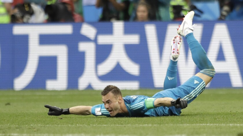 Russia goalkeeper Igor Akinfeev celebrates after his team advanced to the quarterfinal during the ro