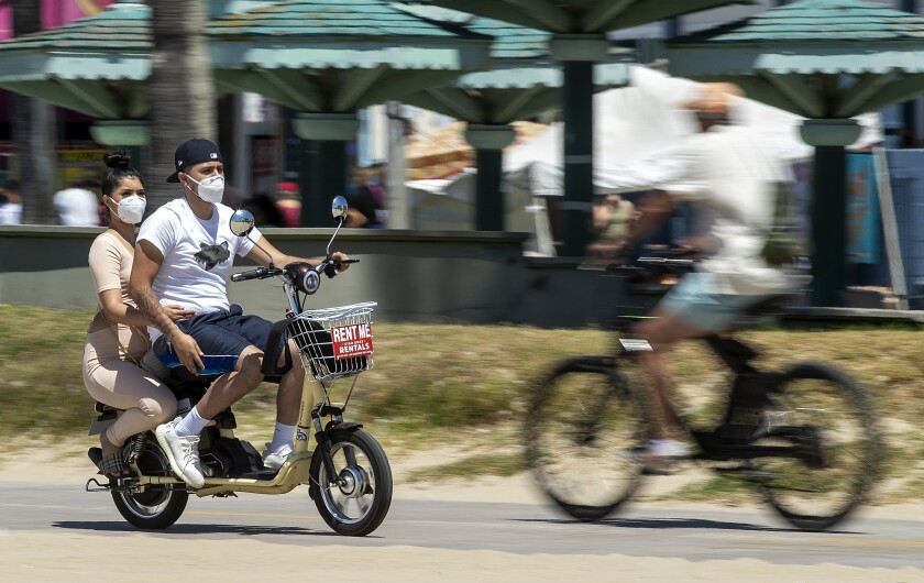 People wear protective masks Sunday while riding on the bicycle path on Venice Beach.