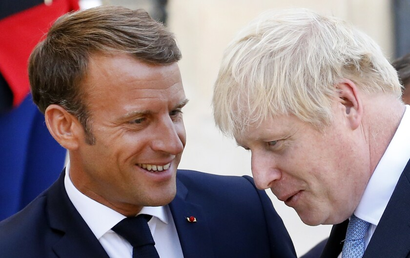 French President Emmanuel Macron accompanies British Prime Minister Boris Johnson after their meeting at the Elysee Presidential Palace on Thursday in Paris. Johnson was on an official visit prior to attending the Group of 7 summit in Biarritz, France.