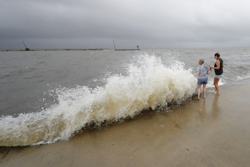 Erin Shaw, left, and Brittany Schanzbach stand near crashing waves near the seawall of Lake Pontchartrain from a storm surge in New Orleans, Sunday, June 7, 2020, as Tropical Storm Cristobal approaches the Louisiana Coast. (AP Photo/Gerald Herbert)
