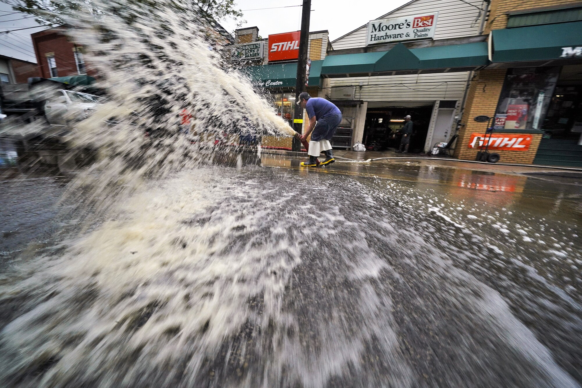 Water sprays dramatically from a pump on a street outside a hardware store.