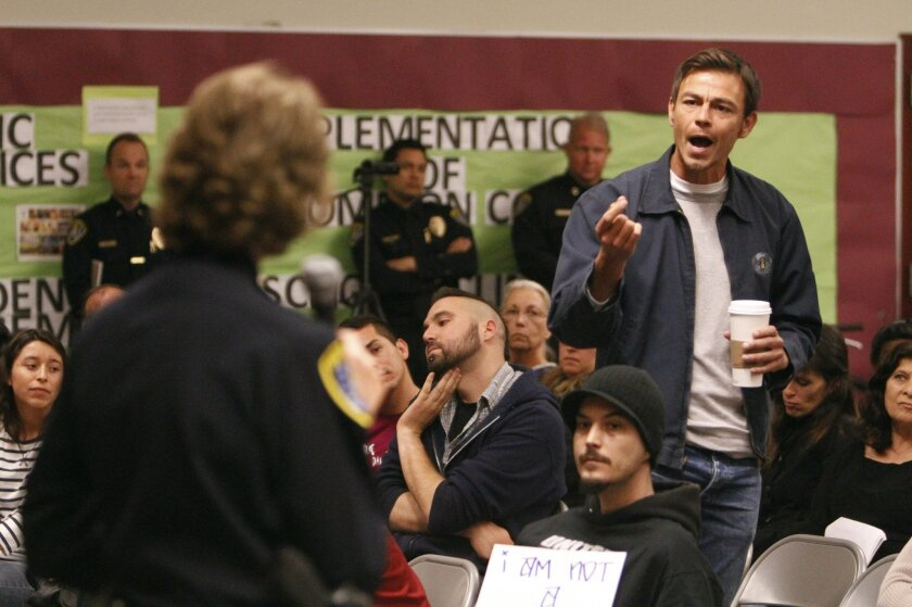 Joshua Funn confronts San Diego Police Chief Shelley Zimmerman about racial profiling by police officers during a town hall meeting by Zimmerman at Cherokee Point Elementary School in City Heights on Wednesday.