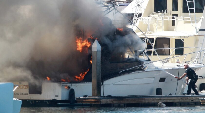 """A 45 foot long 1974 Chris-Craft  boat named """"Escort""""  was consumed by flames at the Cortez Marina on Harbor Island shortly before noon on Wednesday, September 26.  San Diego Harbor Police and San Diego Fire put the fire out."""