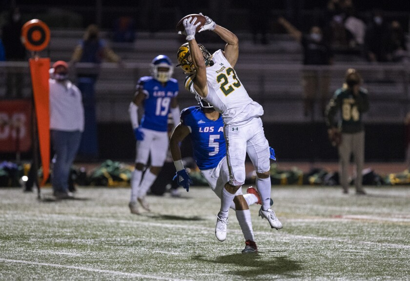 Edison's Nico Brown makes a catch over Los Alamitos' Lane Broderick for a touchdown during a Sunset League game on March 26.