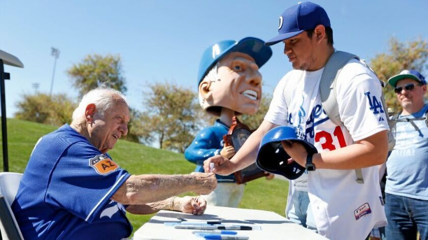 Former Dodgers manager Tommy Lasorda, left, signs an autograph for Alvaro Negrete, 21, of Oxnard, at Dodgers spring training camp in Glendale, Ariz., on Feb. 21.