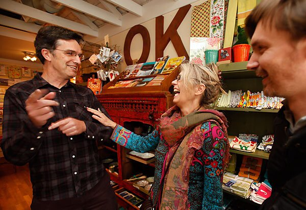 """Arno Hesse, left, and Guillame Lebleu, right, residents of San Francisco's Bernal Heights neighborhood, visit with Darcy Lee, owner of Heartfelt, a store that sells craft items. Hesse and Lebleu came up with the idea of a credit card called Bernal Bucks, a """"complementary currency"""" that allows shoppers to earn credits and give back to the tight-knit community."""