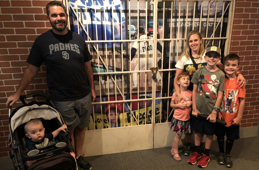 Erin States Hoy and family take a photo near the Baseball Hall of Fame display about the 1994 strike, which features a photo of her as a 10-year-old girl.