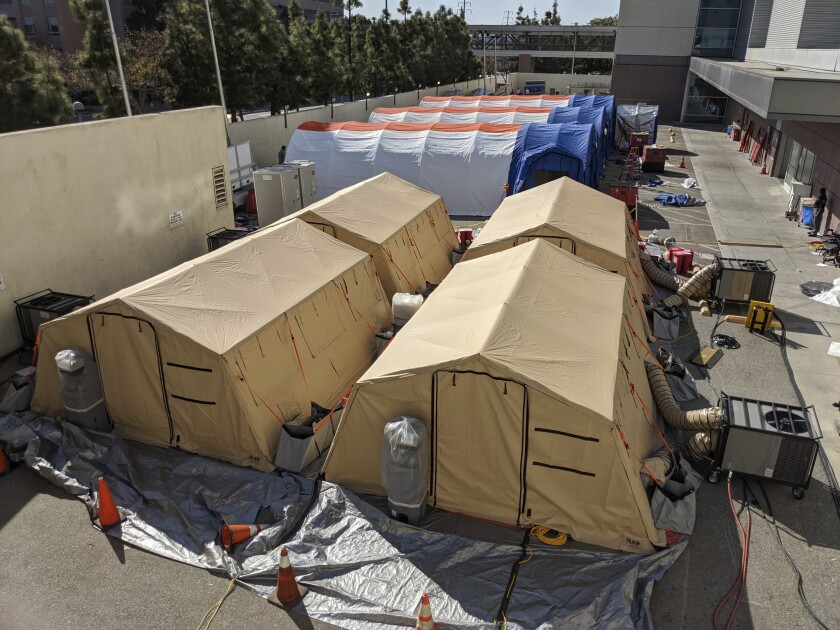 FILE - In this Monday, March 30, 2020, file photo, triage tents are deployed for a possible surge of emergency COVID-19 patients outside of the Los Angeles County + USC Medical Center in Los Angeles. A health official in California's third largest county is urging hospitals to cancel elective surgeries and implement plans for an onslaught of COVID-19 patients, as intensive care units fill up statewide amid spiking virus cases. Dr. Carl Schultz says ambulances have been waiting for hours to unload patients because Orange County emergency rooms are so backed up. (AP Photo/Damian Dovarganes, File)