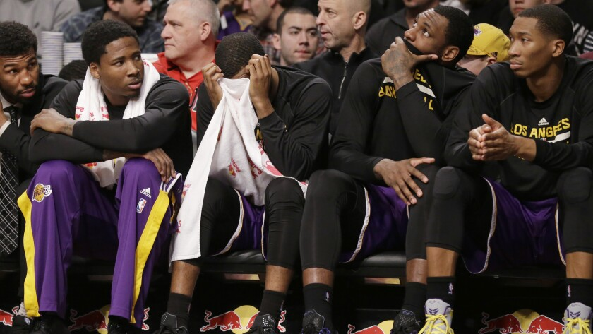 Lakers players , including Ed Davis at left, on the bench react to a call during a 107-99 road loss to the Brooklyn Nets on March 29, 2015.