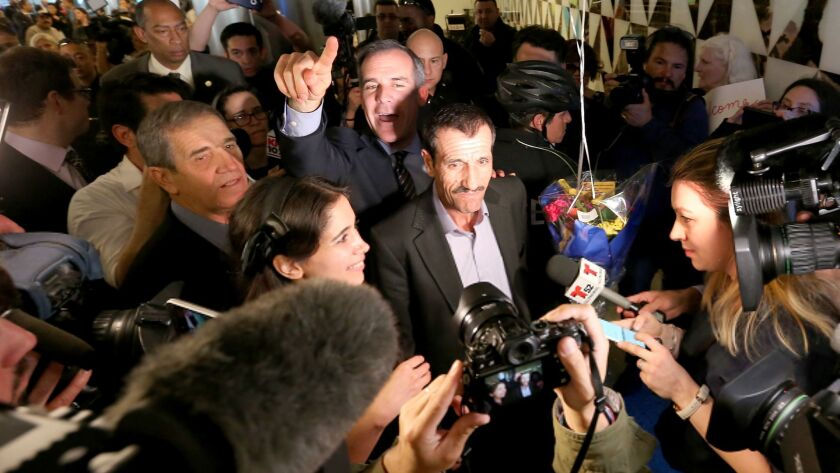 Ali Vayeghan, center, an Iranian citizen with a valid U.S. visa, is swarmed by the media as he is escorted through LAX by L.A. Mayor Eric Garcetti after his arrival.