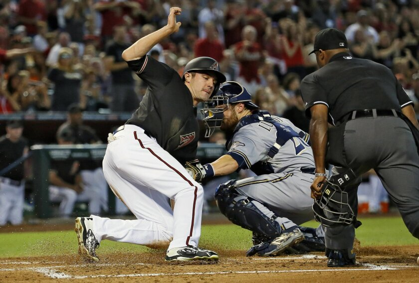 Arizona Diamondbacks' A.J. Pollock scores on an RBI double by teammate Paul Goldschmidt as Milwaukee Brewers catcher Jonathan Lucroy makes the tag during the first inning of a baseball game, Saturday, July 25, 2015, in Phoenix. (AP Photo/Matt York)