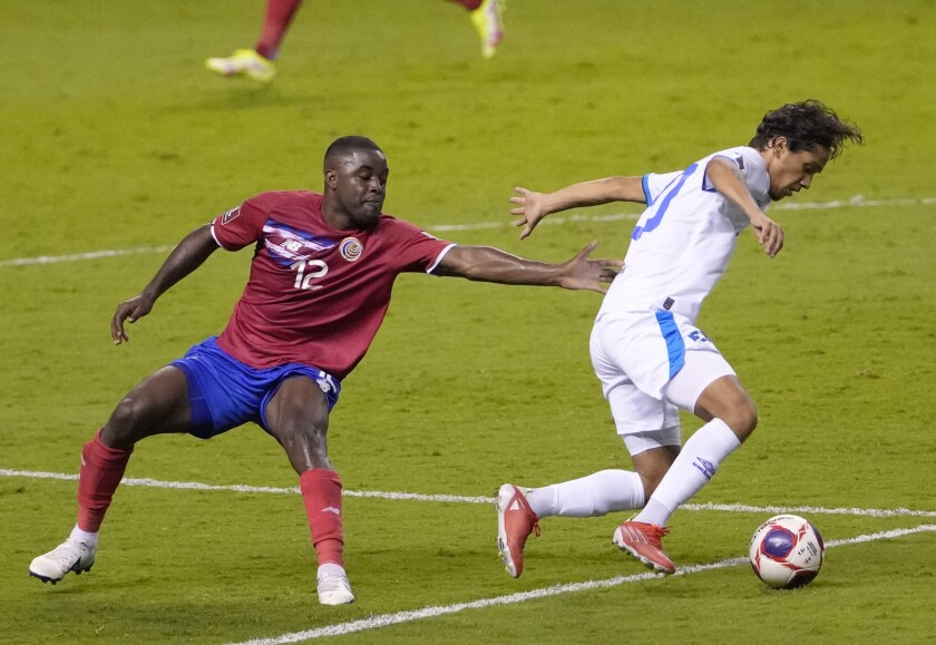 El Salvador's Enrico Duenas, right, and Costa Rica's Joel Campbell battle for the ball during a qualifying soccer match for the FIFA World Cup Qatar 2022 at National stadium in San Jose, Costa Rica, Sunday, Oct. 10, 2021. (AP Photo/Moises Castillo)