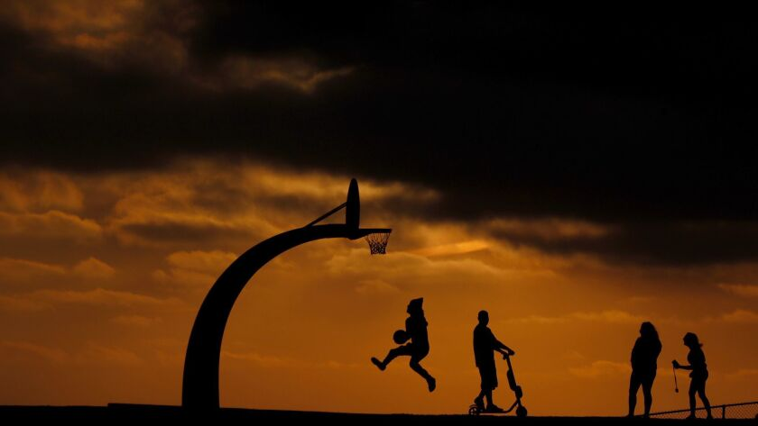 People are silhouetted against a golden sky in Angels Gate Park in Los Angeles on Aug. 23, 2018.
