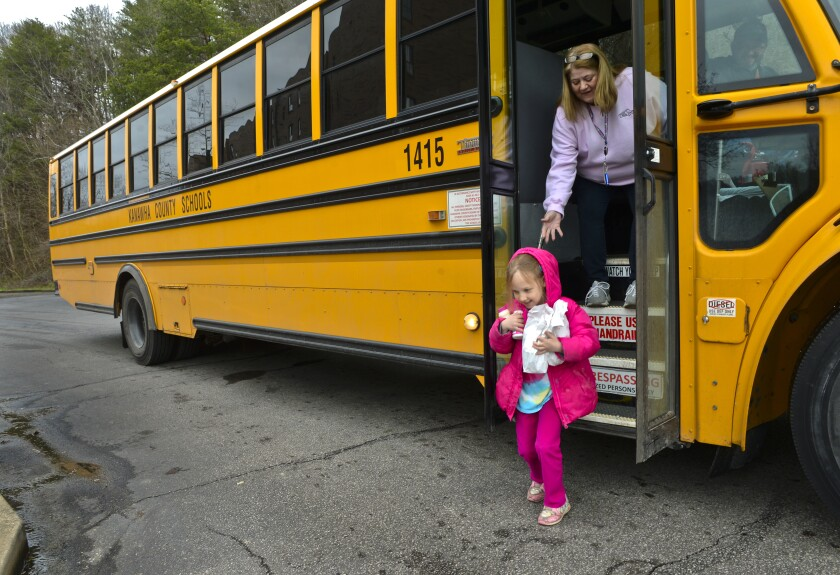 Amira Sexton, 6, of Charleston, W.Va., picks up a breakfast and a lunch that were delivered March 16 by her school bus driver Rob Rider and bus aide Rosemary Light.
