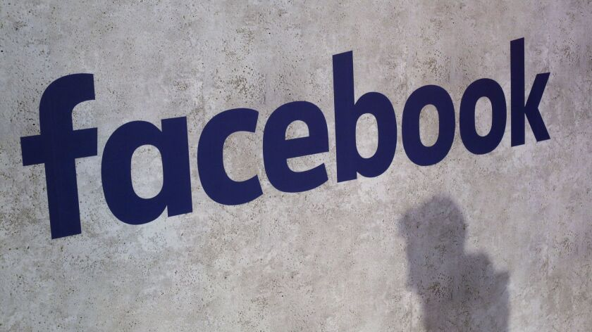 FILE - This Jan. 17, 2017, file photo shows a Facebook logo being displayed in a start-up companies