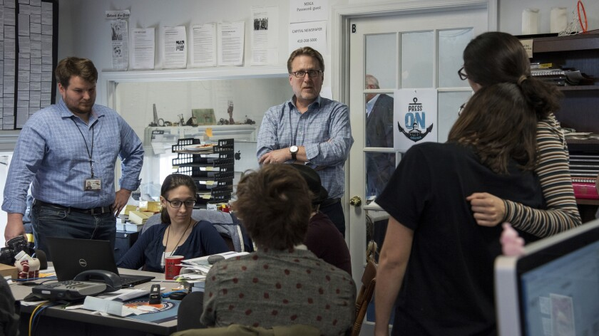 FILE - In this April 25, 2019 file photo, Editor Rick Hutzell, center, gives a speech to his staff including Chase Cook, Nicki Catterlin, Rachael Pacella, Selene San Felice and Danielle Ohl at the Capital Gazette in Annapolis, Md. The editor of the Capital Gazette, which won a special Pulitzer Prize citation for its coverage and courage in the face of a massacre in its newsroom, is leaving the Maryland newspaper. Hutzell, who worked at the Annapolis paper for more than three decades, authored a farewell column that was published on the paper's website Saturday, June 19, 2021. (Ulysses Muoz/The Baltimore Sun via AP)