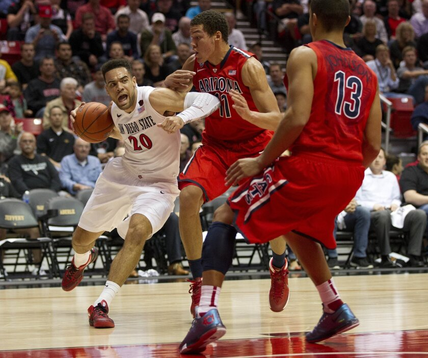 JJ O'Brien tries to split the Arizona defense of Aaron Gordon (11) and Nick Johnson (13) in the first half.