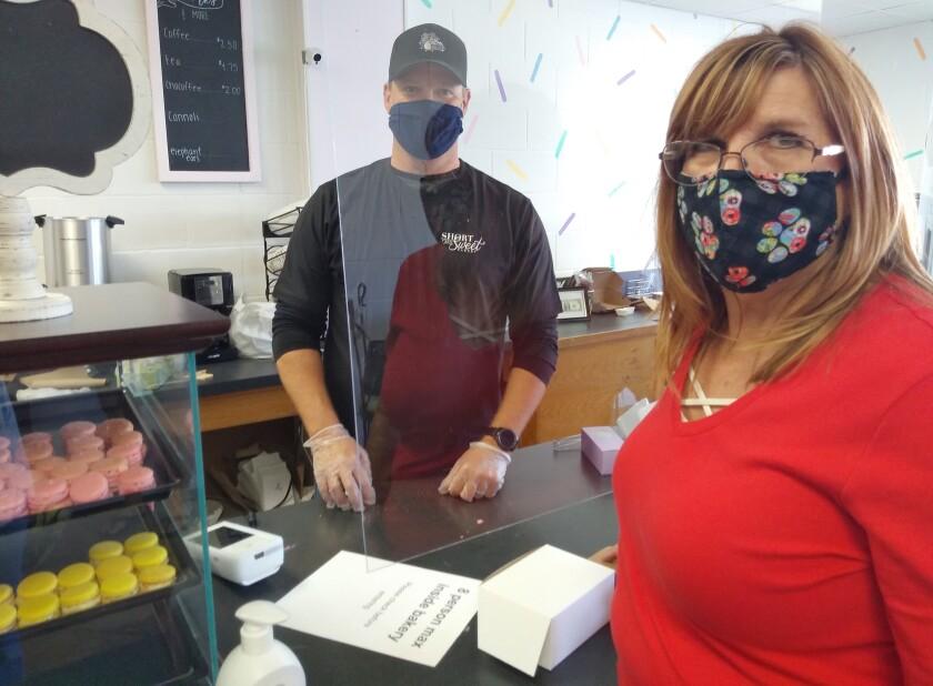 Short and Sweet Bakery co-owner John Zetterberg helps customer Mindy Waldhauser.