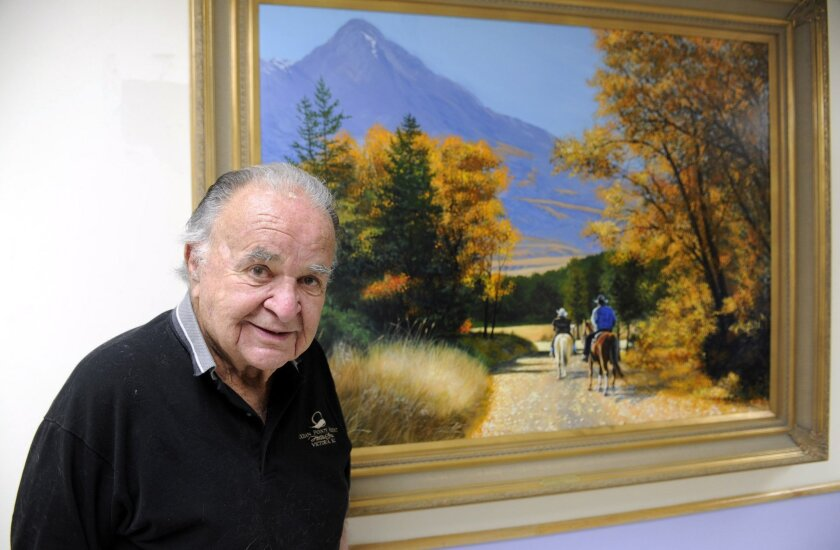 This June 2012 photo shows former 'Mad' magazine editor Al Feldstein standing near one of his paintings at Livingston HealthCare. Feldstein, whose 28 years at the helm of Mad magazine transformed the satirical publication into a pop culture institution, has died, Tuesday, April 29, 2014. He was 88.