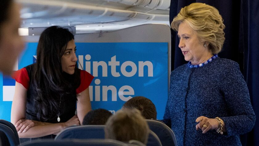 Hillary Clinton and Huma Abedin speak onboard the campaign plane Friday before learning of the FBI's letter to Congress.