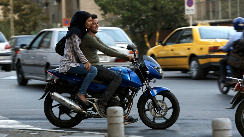 A woman rides on the back of a motorcycle in Tehran.